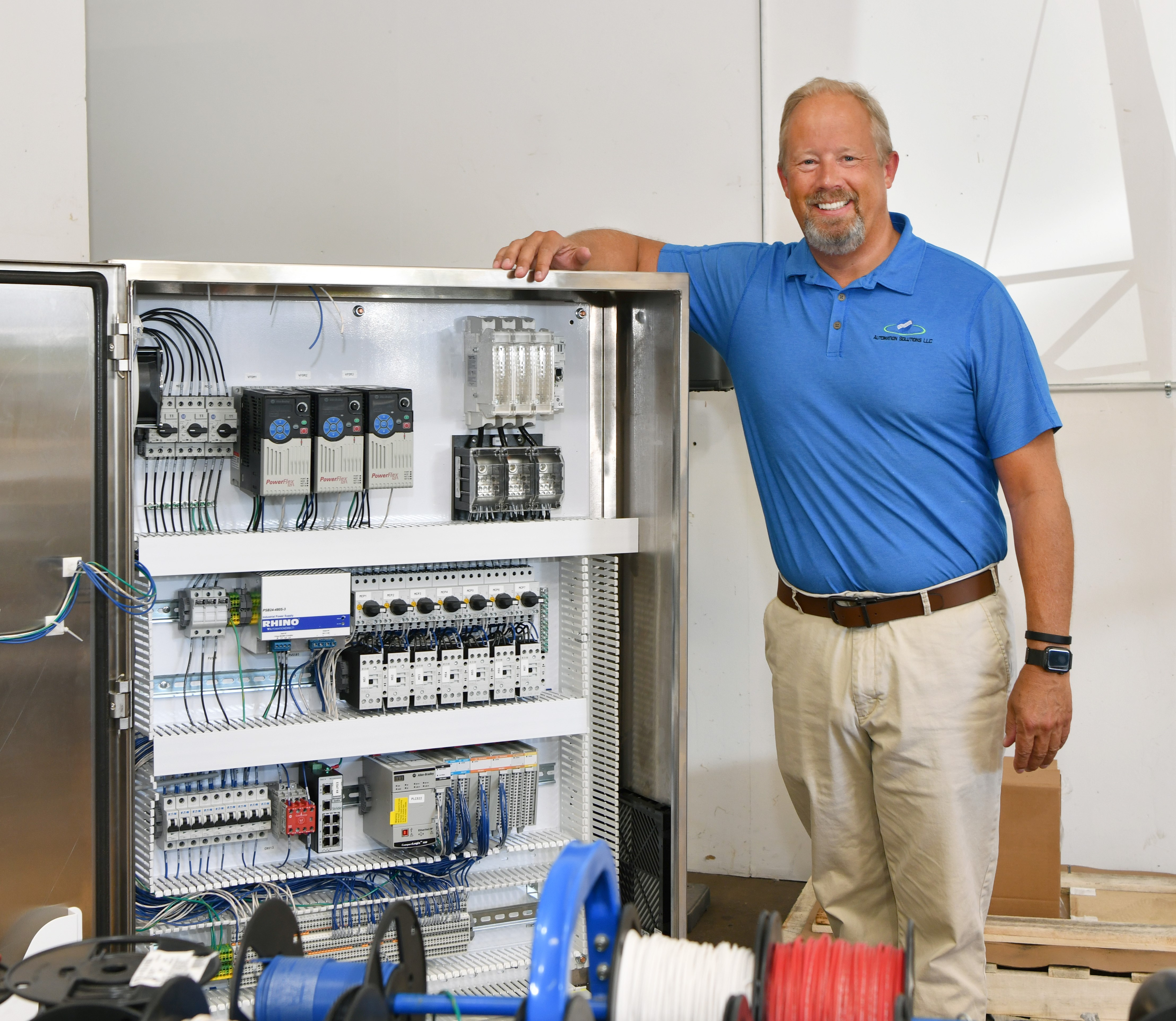 Automation Solutions president Steve Nordness stands next to control panel.